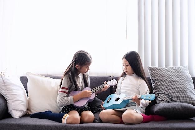 La hermana mayor enseña a la hermana menor a tocar el ukelele, con un sentimiento de interés, en la sala de estar, aprendiendo juntas, luz borrosa alrededor Foto Premium