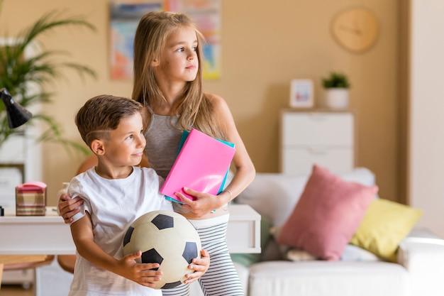 Hermana mayor con su hermano pequeño en la sala de estar Foto gratis