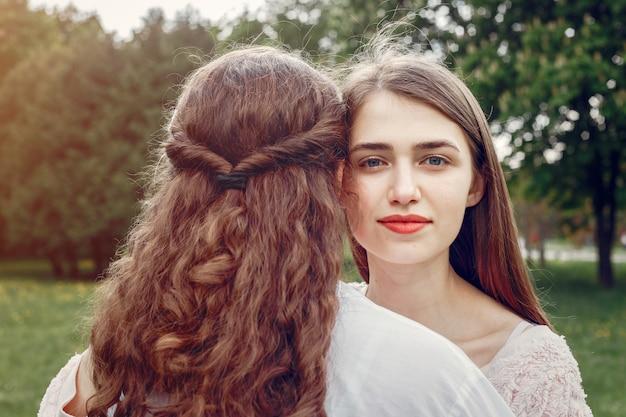 Hermanas elegantes y con estilo en un parque de primavera Foto gratis