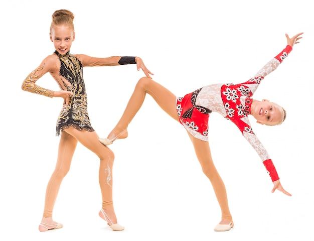 Las hermanas gemelas chicas en chándales demuestran el ejercicio. Foto Premium
