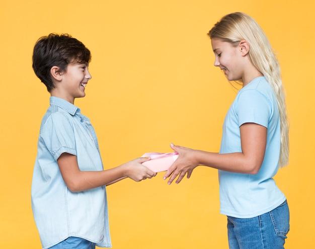 Hermano joven que ofrece un regalo a la hermana Foto gratis