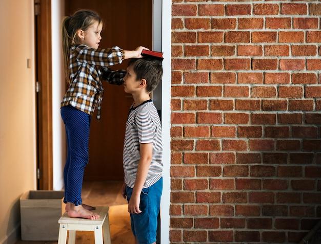 Hermanos comprobando la altura Foto gratis