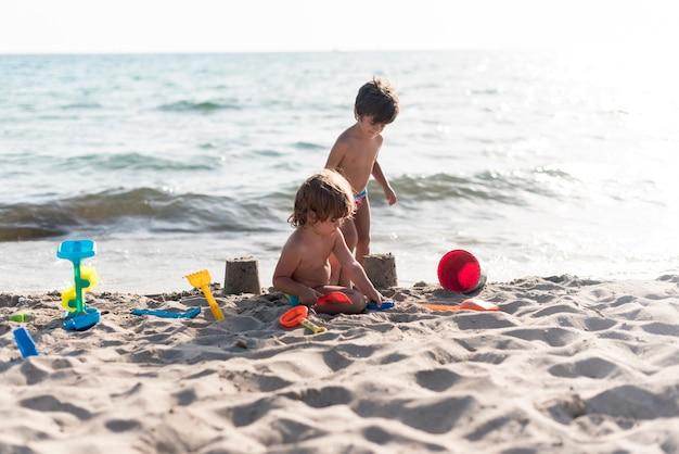 Hermanos haciendo castillos de arena junto al mar. Foto gratis
