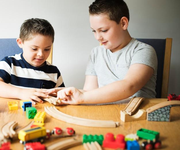 Hermanos jugando con bloques, trenes y coches. Foto Premium