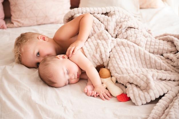Hermanos lindos acostado en la cama Foto gratis