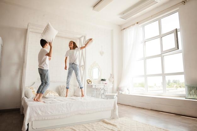 Hermanos que tienen una almohada pelean juntos en la cama en el dormitorio Foto gratis