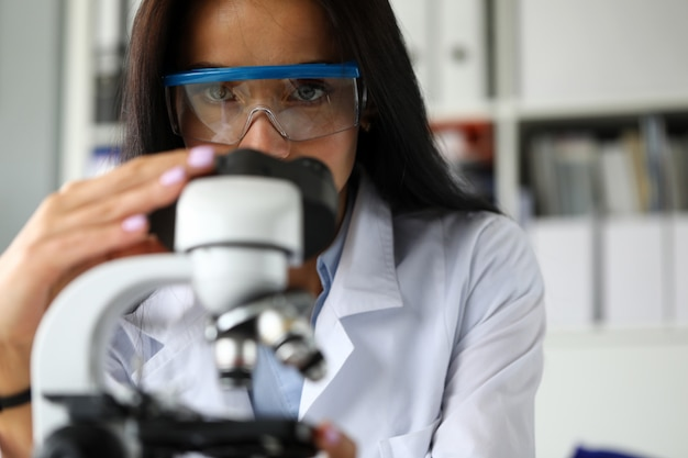 Hermosa asistencia madura usando microscopio científico Foto Premium