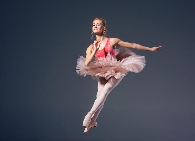 Hermosa bailarina de ballet femenino sobre un fondo gris. bailarina lleva tutú rosa y zapatos de punta. Foto gratis