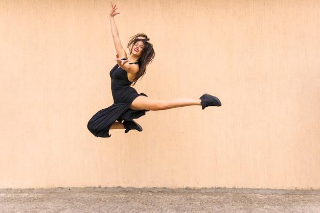 Hermosa bailarina de tango saltando en el aire contra el telón de fondo de la pared Foto gratis