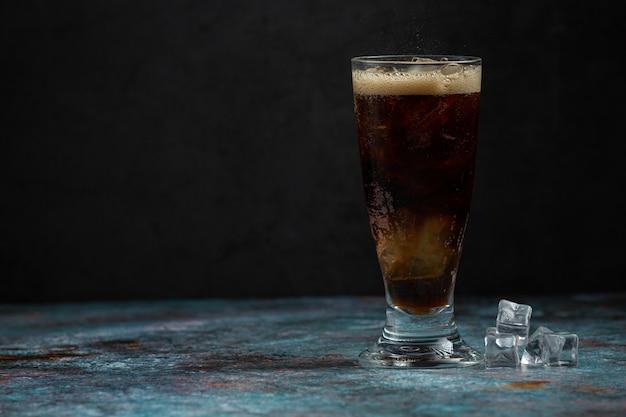 Hermosa bebida fría de cola con cubitos de hielo Foto gratis