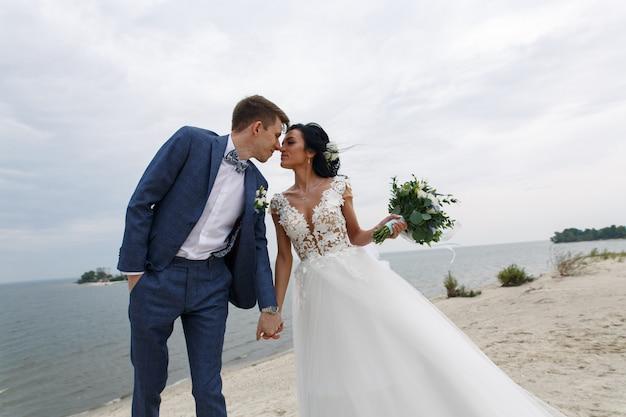 Hermosa boda feliz pareja novia y novio en el día de la boda al aire libre en la playa Foto Premium