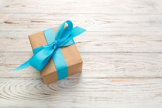 Hermosa caja de regalo con un lazo azul en la mesa de madera blanca. vista superior Foto Premium