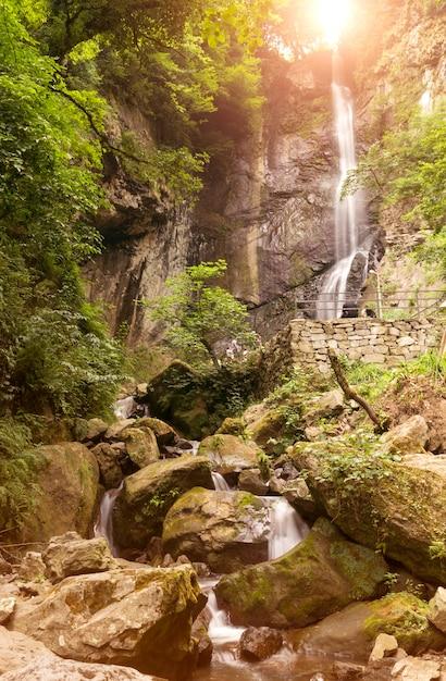 Hermosa cascada al atardecer en el bosque Foto Premium