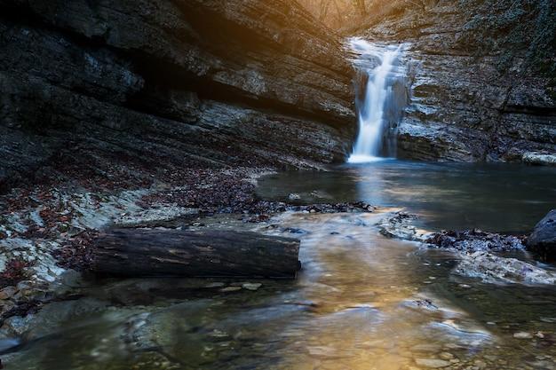 Hermosa cascada en el río de montaña en colorido bosque otoñal con hojas rojas y naranjas al atardecer. paisaje de la naturaleza Foto Premium