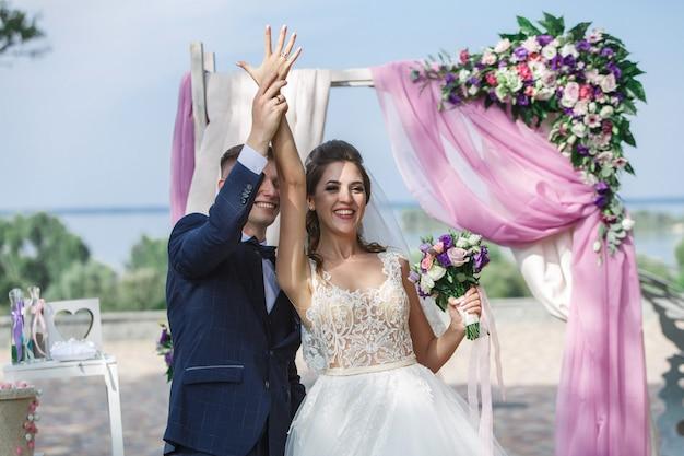 Hermosa ceremonia de boda al aire libre en un día soleado. felices novios intercambian los anillos de boda. Foto Premium