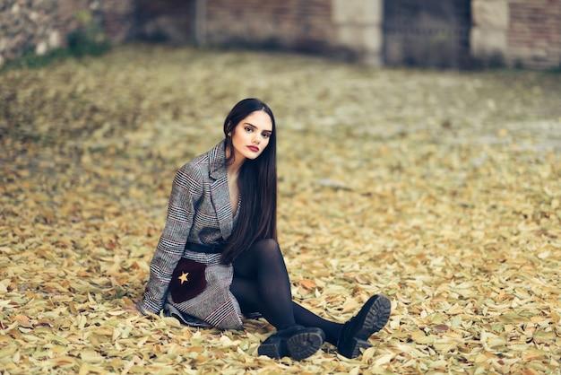 eae49a9998b5 Hermosa chica con abrigo de invierno sentado en el piso de un parque ...