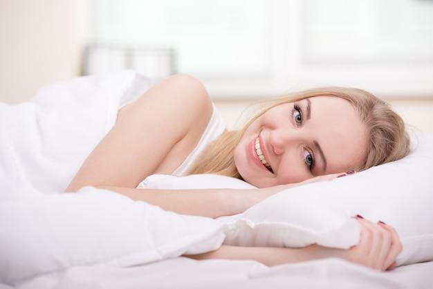Hermosa chica acostada en una cama en su habitación. Foto Premium