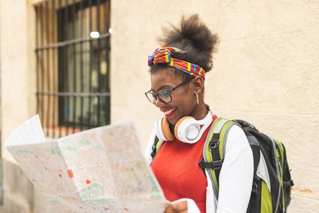 Hermosa chica afroamericana usando un mapa Foto Premium