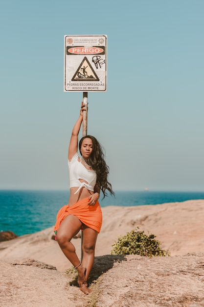 Hermosa chica apoyada contra una señal de peligro en la playa Foto gratis