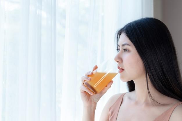 Hermosa chica de belleza asiática linda chica siente feliz bebiendo jugo de naranja para una buena salud en la mañana Foto gratis
