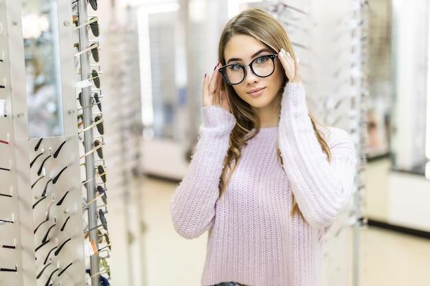 Hermosa chica con cabello largo dorado y apariencia de modelo demuestra la diferencia de gafas en una tienda profesional Foto gratis