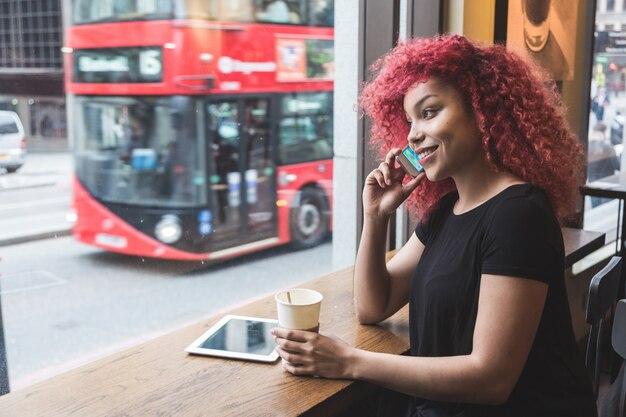 Hermosa chica en un café hablando por teléfono inteligente Foto Premium