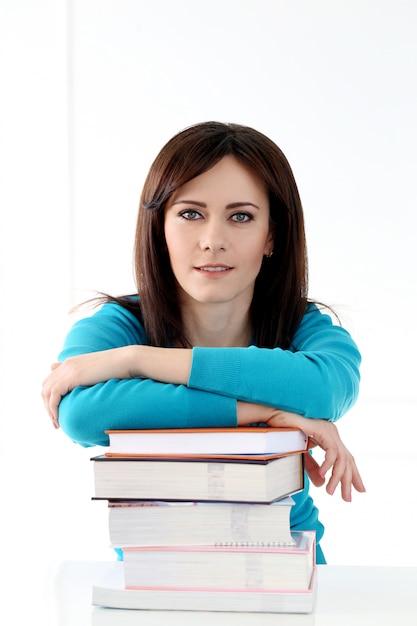 Hermosa chica con camiseta azul y libros Foto gratis
