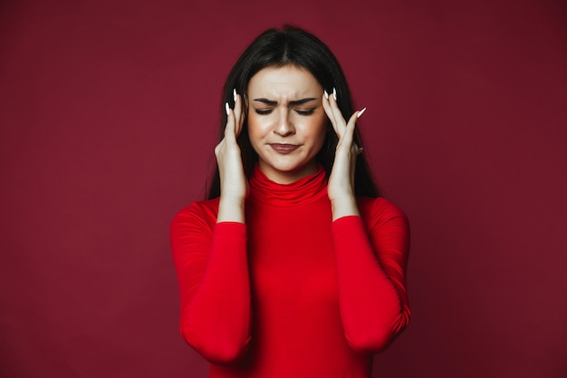 Hermosa chica caucásica morena vestida de jersey rojo con dolor de cabeza doloroso Foto gratis
