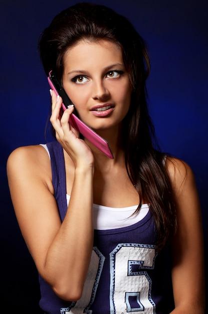 Hermosa chica con celular rosa Foto gratis
