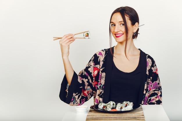 Hermosa chica comiendo un sushi en un estudio Foto gratis