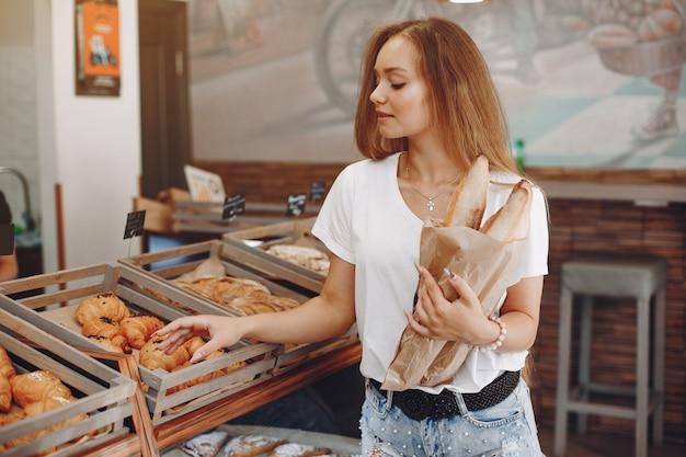 Hermosa chica compra bollos en la panadería Foto gratis