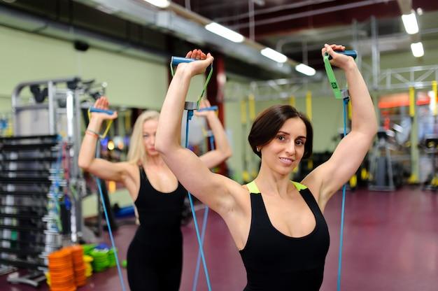 Una hermosa chica se dedica a un gimnasio. Foto Premium
