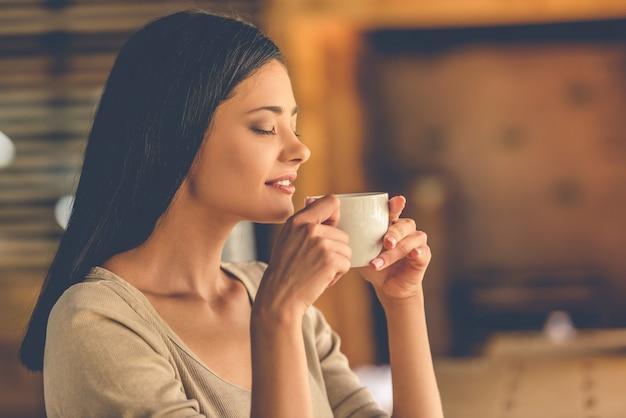 Hermosa chica disfruta el aroma del café Foto Premium