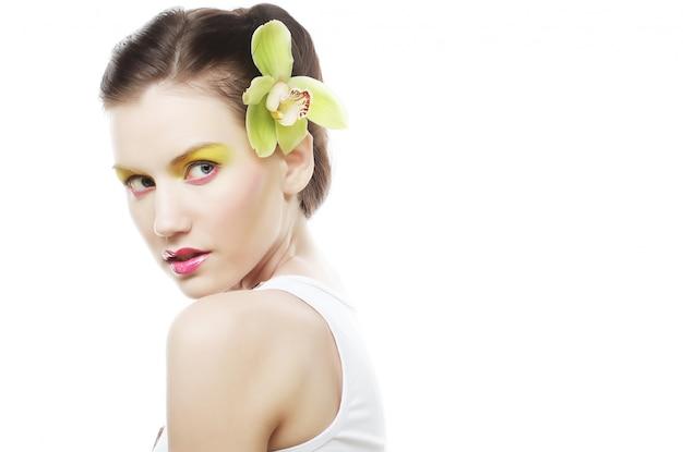 Hermosa chica con estilo con orquídeas phalaenopsis en el cabello. Foto Premium