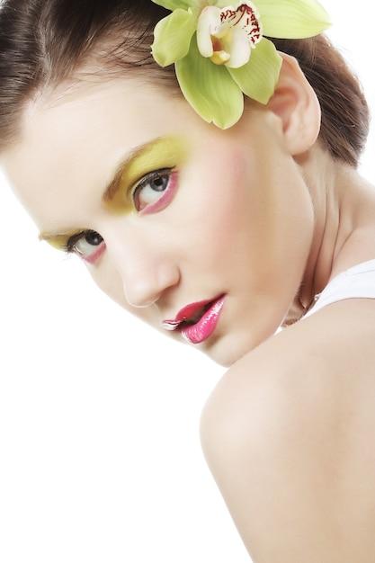 Hermosa chica con estilo con orquídeas phalaenopsis en el cabello Foto Premium