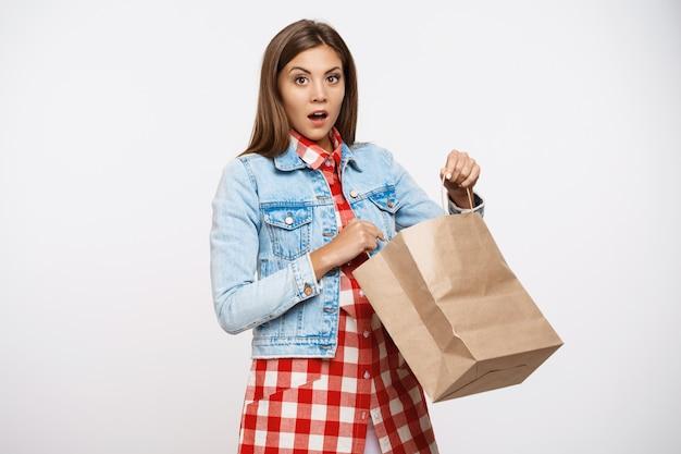 Hermosa chica con estilo que parece sorprendida después de abrir la bolsa de papel Foto gratis