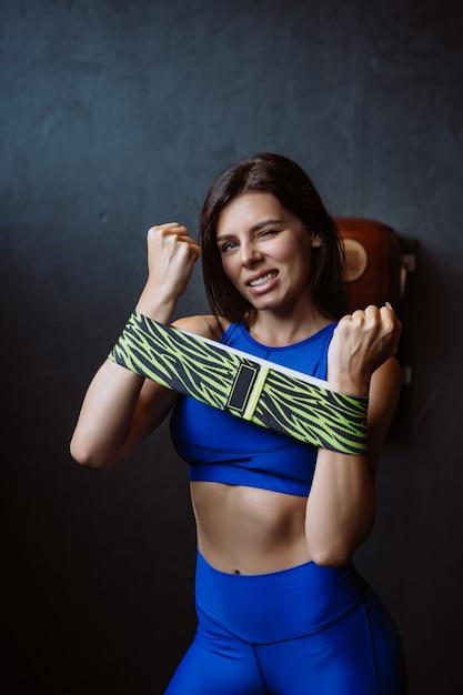 Hermosa chica con una figura deportiva se alza sobre una pared oscura y posa Foto gratis
