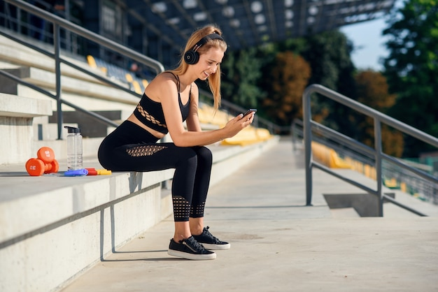 Una hermosa chica de fitness en ropa deportiva gris usa un teléfono inteligente y escucha música en el estadio después del entrenamiento. concepto deportivo y saludable. Foto Premium