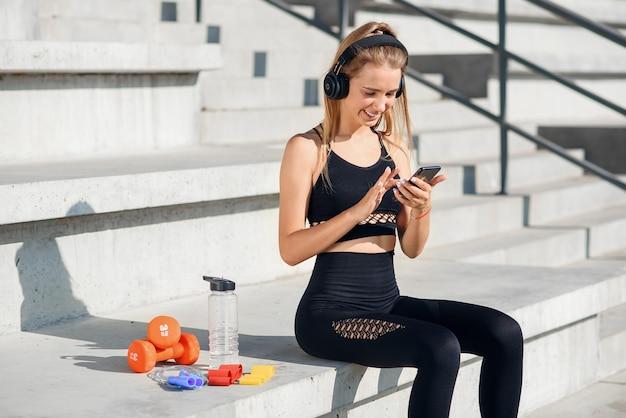 Una hermosa chica de fitness en ropa deportiva gris usa un teléfono inteligente y escucha música en el estadio después del entrenamiento. Foto Premium