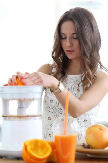 Hermosa chica haciendo jugo de naranja Foto gratis