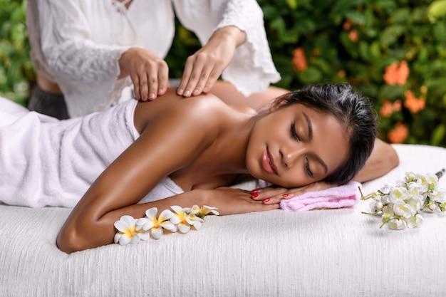 Hermosa chica interracial se acuesta de lado con los ojos cerrados en una mesa de masaje con ramitas de flores y recibe un masaje de espalda Foto Premium