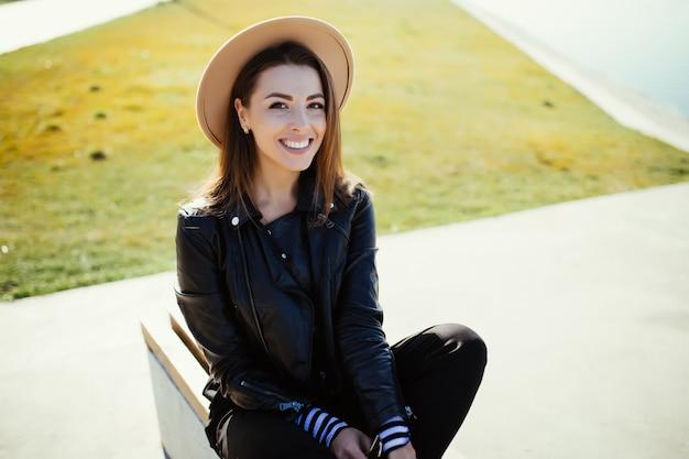 Hermosa chica joven sentada en el parque cerca del lago de la ciudad en un día frío y soleado de verano vestida con ropa negra Foto gratis
