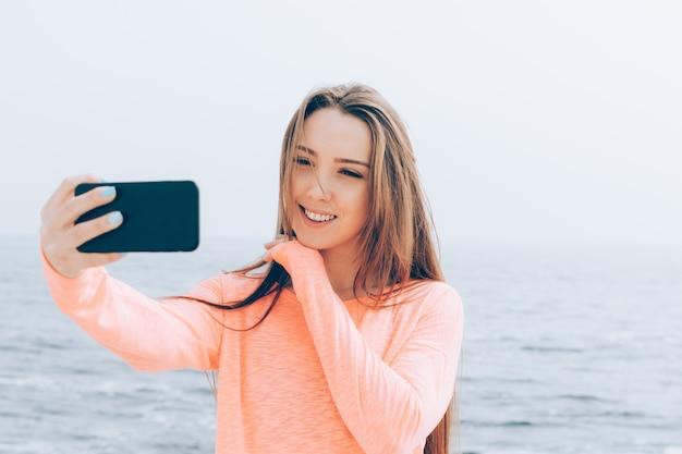 Hermosa chica con largo cabello castaño toma fotos de ella misma en el teléfono en la playa Foto Premium