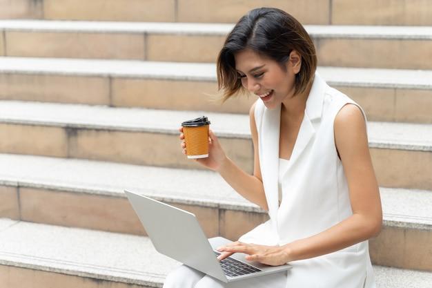 Hermosa chica linda sonriendo en ropa de mujer de negocios usando la computadora portátil en la ciudad urbana Foto gratis