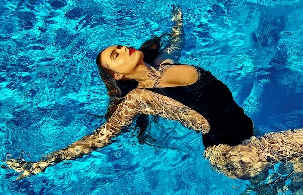 Hermosa chica modelo con cabello oscuro en traje de baño negro Foto gratis