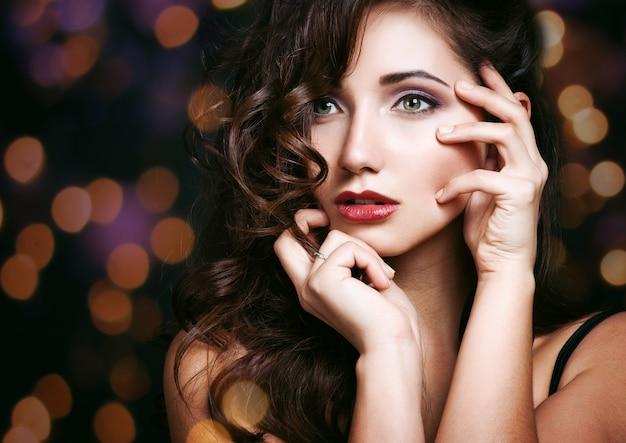Hermosa chica morena. maquillaje saludable para cabello largo y festivo. Foto Premium