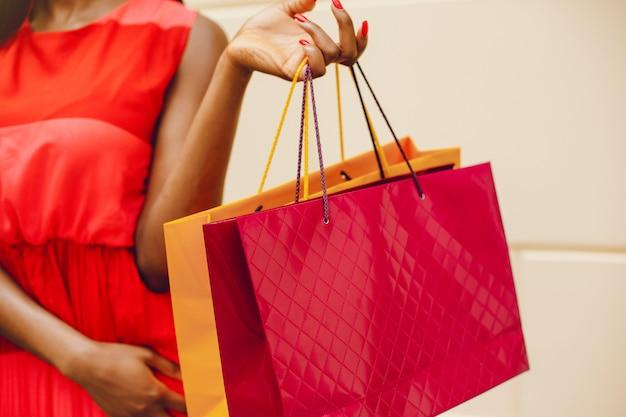 Hermosa chica negra con bolsas de compras en una ciudad Foto gratis