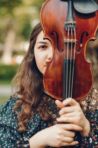 Hermosa chica en un parque de verano con un violín Foto gratis