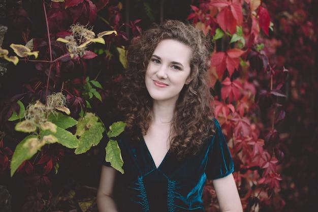 Hermosa chica de pelo rizado en un vestido de terciopelo azul oscuro en un parque de otoño Foto Premium