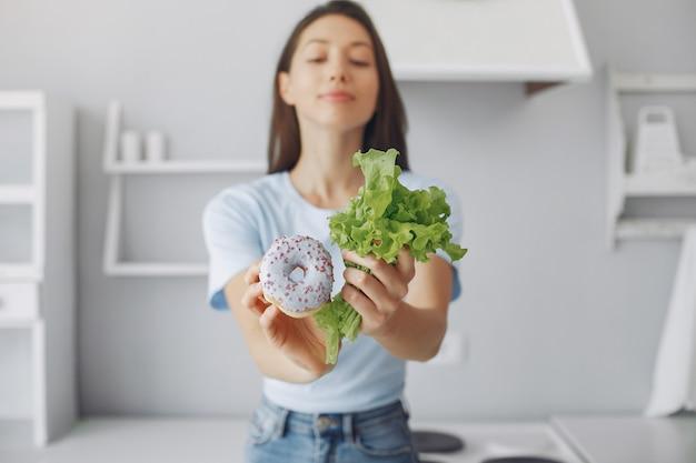Hermosa chica de pie en una cocina con donas y hojas Foto gratis